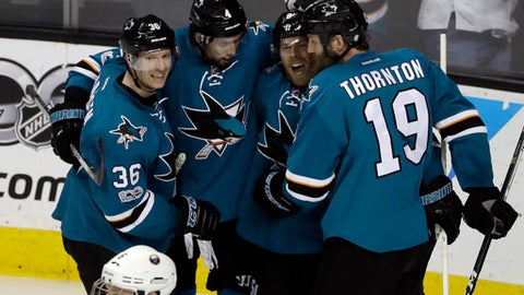 San Jose Sharks' Joe Pavelski, second from right, is hugged by teammates Joe Thornton (19), Brenden Dillon (4) and Jannik Hansen (36) after Pavelski's goal against the Buffalo Sabres during the third period of an NHL hockey game Tuesday, March 14, 2017, in San Jose, Calif. (AP Photo/Marcio Jose Sanchez)