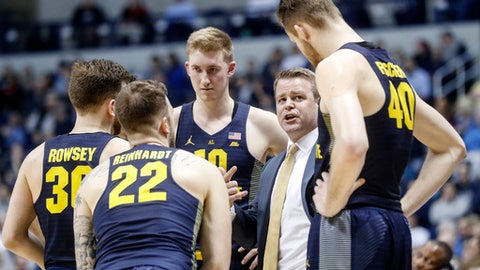 FILE - In this March 1, 2017, file phoot, Marquette head coach Steve Wojciechowski, second from right, directs his players during a time out in the second half of an NCAA college basketball game against Xavier in Cincinnati. In this, the 100th anniversary of Marquette basketball and 40th anniversary of the Al McGuire-coached team winning the national title, current coach Steve Wojciechowski is marking his own important milestone. The Golden Eagles are back in the NCAA tournament after a four-year absence. (AP Photo/John Minchillo, File)