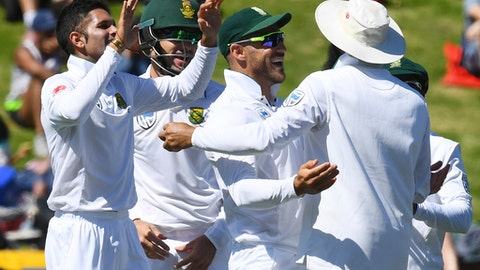 South Africa's Keshav Maharaj, left, celebrates with teammates after dismissing New Zealand's Jeet Raval during the second cricket test at the Basin Reserve, Wellington, New Zealand, Thursday, March 16, 2017. (AP Photo/Ross Setford, SNPA)