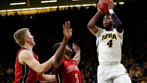 Iowa guard Isaiah Moss, right, shoots over South Dakota's Tyler Peterson, left, and Triston Simpson, (3) during the first half of a first-round game in the NIT college basketball tournament, Wednesday, March 15, 2017, in Iowa City, Iowa. (AP Photo/Charlie Neibergall)