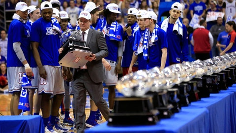 FILE - In this Feb. 22, 2017, file photo, Kansas coach Bill Self carries his 13th Big 12 championship trophy following the team's NCAA college basketball game against TCU in Lawrence, Kan. In the most damaging instance of legal trouble at Kansas this season, police investigated a reported rape at the dorm that houses the basketball team. No charges have been filed. From there, more headlines kept piling up involving no fewer than four players. Self said he's proud his team has rallied despite the steady stream of issues. (AP Photo/Orlin Wagner, File)
