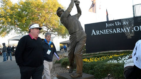 Tim Herron, left, winner of the 1999 Arnold Palmer Invitational golf tournament, walks past a statue erected in honor of the golfing legend for which the tournament is named, during the first round of tournament in Orlando, Fla., Thursday, March 16, 2017. (AP Photo/Phelan M. Ebenhack)