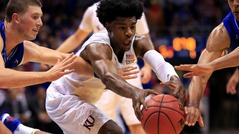 FILE - In this Nov. 25, 2016, file photo, Kansas guard Josh Jackson, center, gets to the ball before UNC-Asheville guards Kevin Vannatta, left, and MaCio Teague, right, during the first half of an NCAA college basketball game in Lawrence, Kan. Kansas has been among the top-ranked teams in college basketball all season, but it enters the NCAA Tournament following an early exit in the Big 12 Conference Tournament _ and with freshman Josh Jackson's legal issues lingering as a possible distraction.  (AP Photo/Orlin Wagner, File)