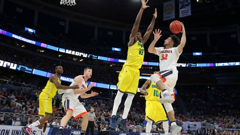 Virginia guard London Perrantes (32) goes up for a shot against Devontae Cacok (15) during the second half of a first-round men's college basketball game in the NCAA Tournament, Thursday, March 16, 2017, in Orlando, Fla. Virginia defeated UNC Wilmington 76-71. (AP Photo/Gary McCullough)