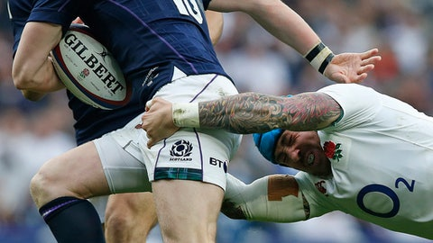 FILE- In this file photo dated Saturday March 11, 2017, England's Jack Nowell, right, tackles Scotland's Finn Russell during the Six Nations rugby union international  at Twickenham stadium in London.  England's rugby players are heading to Dublin on Saturday March 18, 2017, aiming to achieve greatness with back-to-back Grand Slams in the Six Nations and a tier-one world record of 19 straight wins. (AP Photo/Alastair Grant, FILE)