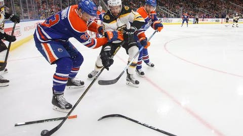 Boston Bruins' Drew Stafford (19) battles for the puck with Edmonton Oilers' Matthew Benning (83) and Jordan Eberle (14) during the third period of an NHL hockey game in Edmonton, Alberta, Thursday, March 16, 2017. (Jason Franson/The Canadian Press via AP)
