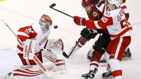 Detroit Red Wings goalie Petr Mrazek (34) makes a save on a shot as Red Wings defenseman Danny DeKeyser (65) shoves Arizona Coyotes left wing Jordan Martinook (48) during overtime of an NHL hockey game Thursday, March 16, 2017, in Glendale, Ariz. The Red Wings defeated the Coyotes 5-4 in a shootout. (AP Photo/Ross D. Franklin)