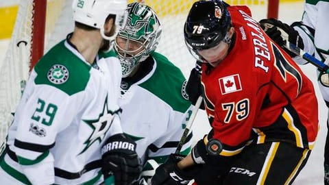 Dallas Stars' Greg Pateryn, left, and goalie Kari Lehtonen, centrer, of Finland, look for the puck as it bounces off Calgary Flames' Micheal Ferland during the second period of an NHL hockey game in Calgary, Alberta, Friday, March 17, 2017. (Jeff McIntosh/The Canadian Press via AP)