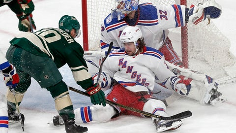 New York Rangers' Mats Zuccarello falls against goalie Antti Raanta, right,  while Minnesota Wild's Jordan Schroeder, left, positions himself during the second period of an NHL hockey game Saturday, March 18, 2017, in St. Paul, Minn. (AP Photo/Jim Mone)