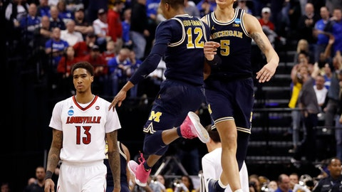 Michigan's D.J. Wilson (5) and teammate Muhammad-Ali Abdur-Rahkman (12) celebrate as Louisville's Ray Spalding (13) walks past following a second-round game in the men's NCAA college basketball tournament Sunday, March 19, 2017, in Indianapolis. Michigan won 73-69. (AP Photo/Jeff Roberson)