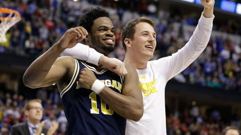 Michigan guard Derrick Walton Jr. (10) and guard Andrew Dakich (11) celebrate following a 73-69 win over Louisville in a second-round game in the men's NCAA college basketball tournament in Indianapolis, Sunday, March 19, 2017.  (AP Photo/Michael Conroy)