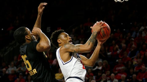 Richmond's Khwan Fore, right, lines up a shot while Oakland's Martez Walker attempts to block him during a second-round NIT NCAA men's college basketball game Sunday, March 19, 2017, in Richmond, Va. (Shelby Lum/Richmond Times-Dispatch via AP)