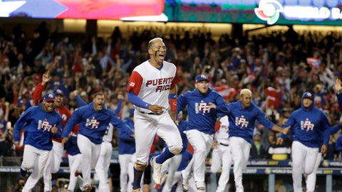 Puerto Rico's Carlos Correa celebrates after scoring in winning run on a hit by Eddie Rosario in the 11th inning of a semifinal against the Netherlands in the World Baseball Classic in Los Angeles, Monday, March 20, 2017. (AP Photo/Chris Carlson)