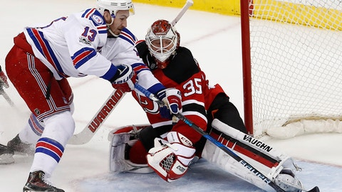 New Jersey Devils goalie Cory Schneider (35) blocks a shot by New York Rangers center Kevin Hayes (13) during overtime of an NHL hockey game, Tuesday, March 21, 2017, in Newark, N.J. The Devils won 3-2. (AP Photo/Julio Cortez)