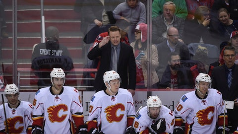 Calgary Flames head coach Glen Gulutzan looks at play against the Washington Capitals from the bench during the third period of an NHL hockey game, Tuesday, March 21, 2017, in Washington. Washington won, 4-2. (AP Photo/Molly Riley)