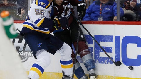 St. Louis Blues defenseman Colton Parayko, left, checks Colorado Avalanche defenseman Erik Johnson into he boards as they battle for the puck in the third period of an NHL hockey game Tuesday, March 21, 2017, in Denver. The Blues won 4-2. (AP Photo/David Zalubowski)