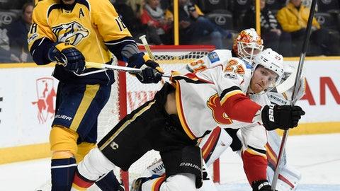 Nashville Predators right wing James Neal (18) shoves Calgary Flames defenseman Dougie Hamilton (27) to the ice during the second period of an NHL hockey game Thursday, March 23, 2017, in Nashville, Tenn. (AP Photo/Mark Zaleski)