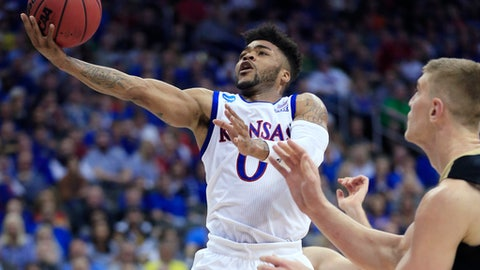 Kansas guard Frank Mason III drives to the basket next to Purdue center Isaac Haas during the second half of a regional semifinal of the NCAA men's college basketball tournament, Thursday, March 23, 2017, in Kansas City, Mo. (AP Photo/Orlin Wagner)