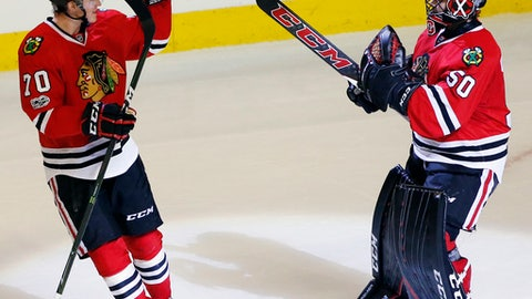 Chicago Blackhawks goalie Corey Crawford, right, celebrates with center Dennis Rasmussen after they defeated the Dallas Stars 3-2 in a shootout during an NHL hockey game Thursday, March 23, 2017, in Chicago. (AP Photo/Nam Y. Huh)