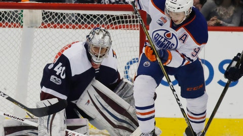 Edmonton Oilers center Ryan Nugent-Hopkins, right, pursues the puck after Colorado Avalanche goalie Jeremy Smith made a stop in the third period of an NHL hockey game Thursday, March 23, 2017, in Denver. Edmonton won 7-4. (AP Photo/David Zalubowski)