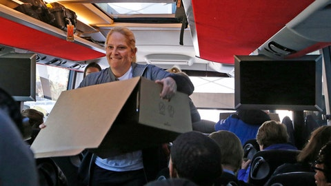 Maryland coach Brenda Frese squeezes through a narrow aisle with a box of food in the team's cramped bus, Thursday, March 23, 2017, after the team arrived in Stamford, Conn., for this weekend's Bridgeport Regional in the NCAA women's college basketball tournament. (AP Photo/Kathy Willens)