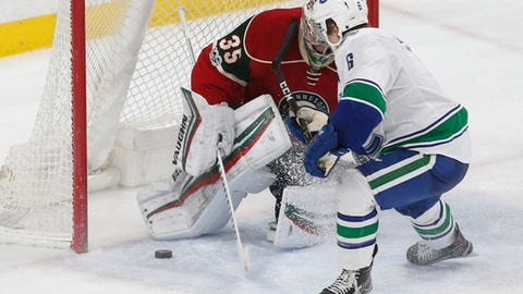 Vancouver Canucks' Brock Boeser, left, who was signed the day before, scores against Minnesota Wild goalie Darcy Kuemper as he made his NHL debut during the second period of an NHL hockey game Saturday, March 25, 2017, in St. Paul, Minn. (AP Photo/Jim Mone)