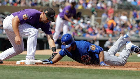 Chicago Cubs' Matt Szczur, right, dives safely back to first as Colorado Rockies' Mark Reynolds applies the tag during the second inning of a spring training baseball game Saturday, March 25, 2017, in Scottsdale, Ariz. (AP Photo/Darron Cummings)