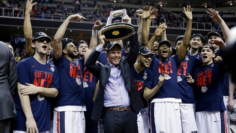 Gonzaga head coach Mark Few, center, holds a trophy as his players surround him after a win over Xavier in an NCAA Tournament college basketball regional final game Saturday, March 25, 2017, in San Jose, Calif. (AP Photo/Ben Margot)