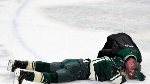 Minnesota Wild left wing Zach Parise (11) is looked at by a trainer after a high stick to the face by Washington Capitals right wing Tom Wilson (not pictured) during the first period of an NHL hockey game, Tuesday, March 28, 2017, in St. Paul, Minn. (AP Photo/Hannah Foslien)
