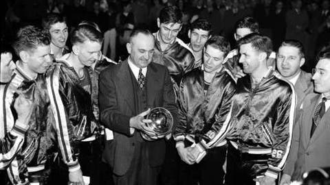 FILE - In this March 26, 1949, file photo, University of Kentucky basketball coach Adolph Rupp and his team admire the NCAA basketball title cup after defeating Oklahoma A&M 46-36 in Seattle. Front row, left to right are: Jim Line, Walter Hirsch, Coach Rupp; Ralph Beard, and Clifford Barker. Star center Alex Groza looks over Rupp's shoulder. The Associated Press is ranking the top 100 college basketball programs of all time using 68 years of data from the AP Top 25 poll. (AP Photo/Paul Wagner, File)