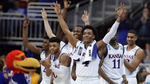 Kansas guard Devonte' Graham, center, celebrates with teammates during the second half of a regional semifinal against Purdue in the NCAA men's college basketball tournament, Thursday, March 23, 2017, in Kansas City, Mo. Kansas won 93-66. (AP Photo/Charlie Riedel)