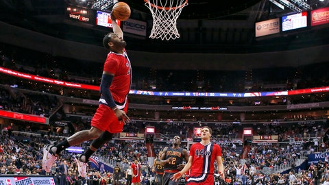 Washington Wizards guard John Wall (2) dunks in front of Atlanta Hawks forward Taurean Prince (12) and Wizards guard Bojan Bogdanovic (44) during the second half of an NBA basketball game Wednesday, March 22, 2017, in Washington. The Wizards won 104-100. (AP Photo/Alex Brandon)