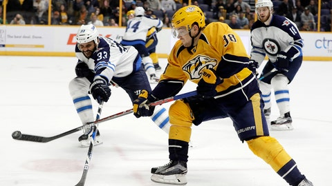 Winnipeg Jets defenseman Dustin Byfuglien (33) and Nashville Predators left wing Viktor Arvidsson (38), of Sweden, reach for the puck during the second period of an NHL hockey game, Monday, March 13, 2017, in Nashville, Tenn. (AP Photo/Mark Humphrey)