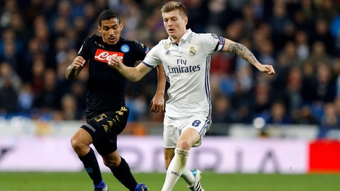 Real Madrid's Toni Kroos, right, runs with the ball followed by Napoli's Allan during the Champions League round of 16, first leg, soccer match between Real Madrid and Napoli at the Santiago Bernabeu stadium in Madrid, Wednesday Feb. 15, 2017. (AP Photo/Francisco Seco)