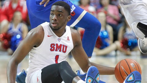 SMU guard Shake Milton (1) dribbles the ball while sitting on the floor as Tulsa forward Junior Etou looks to make a steal during the second half of an NCAA college basketball game, Thursday, March 2, 2017, in Dallas. (AP Photo/Tim Sharp)