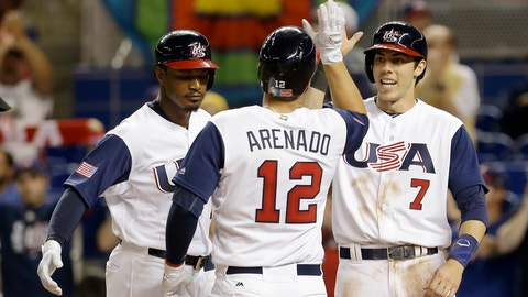 United States' Adam Jones, left, and Christian Yelich (7) congratulate teammate Nolan Arenado (12) after hitting a three-run home run against Canada in the second inning in a first-round game of the World Baseball Classic, Sunday, March 12, 2017, in Miami. (AP Photo/Alan Diaz)