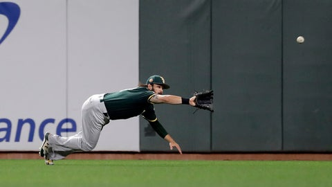 Oakland Athletics center fielder Jaff Decker makes a diving catch on a pop fly from San Francisco Giants' Chris Marrero during the seventh inning of an exhibition baseball game Friday, March 31, 2017, in San Francisco. (AP Photo/Marcio Jose Sanchez)