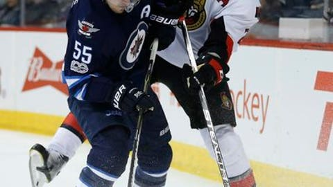 Ottawa Senators' Dion Phaneuf (2) attempts to clear the puck as Winnipeg Jets' Mark Scheifele (55) applies pressure during second-period NHL hockey game action in Winnipeg, Manitoba, Saturday, April 1, 2017. (John Woods/The Canadian Press via AP)