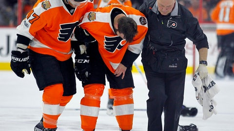 Philadelphia Flyers' Radko Gudas, center, is helped of the ice by Andrew MacDonald, left, and a member of the training staff after an incident involving New Jersey Devils' Dalton Prout, who received a game misconduct for interference during the second period of an NHL hockey game, Saturday, April 1, 2017, in Philadelphia. The Flyers won 3-0. (AP Photo/Tom Mihalek)