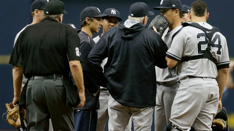 New York Yankees starting pitcher Masahiro Tanaka, second from right, of Japan, talks to catcher Gary Sanchez and pitching coach Larry Rothschild as he struggles during the first inning of a baseball game against the Tampa Bay Rays, Sunday, April 2, 2017, in St. Petersburg, Fla. (AP Photo/Chris O'Meara)