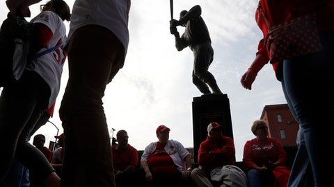 Fans walk past a statue of St. Louis Cardinals great Stan Musial outside Busch Stadium before a baseball game between the Cardinals and the Chicago Cubs on opening day Sunday, April 2, 2017, in St. Louis. (AP Photo/Jeff Roberson)