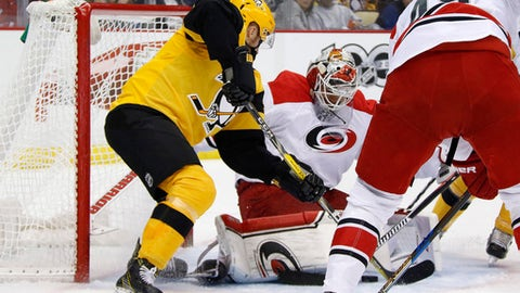 Pittsburgh Penguins' Scott Wilson, left, pokes a rebound under the pads of Carolina Hurricanes goalie Eddie Lack (31) for a goal in the second period of an NHL hockey game in Pittsburgh, Sunday, April 2, 2017. (AP Photo/Gene J. Puskar)