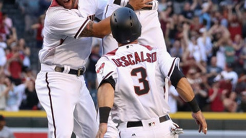 PHOENIX, AZ - APRIL 02:  Chris Owings #16 of the Arizona Diamondbacks celebrates with David Peralta #6 and Daniel Descalso #3 after Owings hit the game winning RBI single against the San Francisco Giants during the ninth inning of the MLB opening day game at Chase Field on April 2, 2017 in Phoenix, Arizona.  (Photo by Christian Petersen/Getty Images)