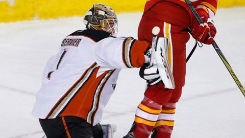 Anaheim Ducks goalie Jonathan Bernier, left, makes a save next to Calgary Flames' Matthew Tkachuk during the first period of an NHL hockey game Sunday, April 2, 2017, in Calgary, Alberta. (Larry MacDougal/The Canadian Press via AP)