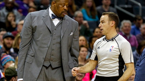 FILE - In this Jan. 28, 2017, file photo, Charlotte Hornets assistant coach Patrick Ewing, left, talks to NBA referee Josh Tiven as the Hornets play the Sacramento Kings in a NBA basketball game in Charlotte, N.C. A person with direct knowledge of the situation says former Georgetown star Patrick Ewing has been hired to coach the school's basketball team, more than two decades after he led the Hoyas to their only national championship as a player. The person spoke to The Associated Press on condition of anonymity because the school has not announced the hire.AP Photo/Nell Redmond, File)