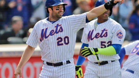New York Mets' Neil Walker (20), left, reacts after scoring on a double hit by Lucas Duda during the seventh inning of an opening day baseball game against the Atlanta Braves at Citi Field, Monday, April 3, 2017, in New York. (AP Photo/Seth Wenig)