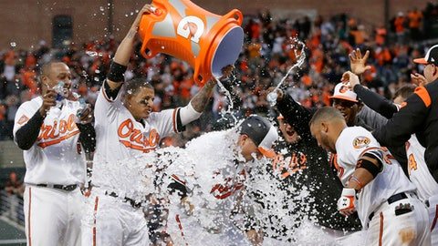 Baltimore Orioles' Mark Trumbo, center, is doused with ice water by teammates as he runs crosses home plate after hitting a solo home run in the 11th inning of an opening day baseball game against the Toronto Blue Jays in Baltimore, Monday, April 3, 2017. Baltimore won 3-2 in 11 innings. (AP Photo/Patrick Semansky)