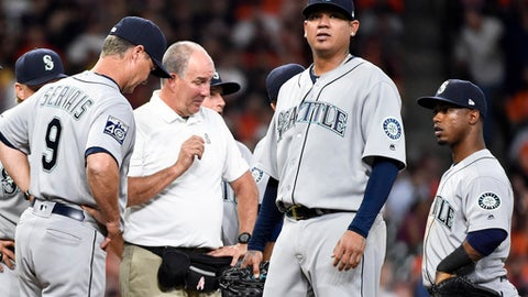 Seattle Mariners starting pitcher Felix Hernandez, second from right, is checked out by manager Scott Servais (9) and a trainer in the fourth inning of a baseball game against the Houston Astros, Monday, April 3, 2017, in Houston. (AP Photo/Eric Christian Smith)