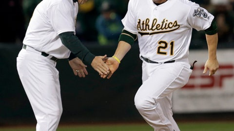 Oakland Athletics' Stephen Vogt, right, is congratulated by third base coach Chip Hale after hitting a home run off Los Angeles Angels' Ricky Nolasco in the second inning of a baseball game, Monday, April 3, 2017, in Oakland, Calif. (AP Photo/Ben Margot)