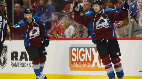 Colorado Avalanche defenseman Erik Johnson, right, celebrates scoring the game-winning goal with left wing J.T. Compher in overtime of an NHL hockey game against the Chicago Blackhawks late Tuesday, April 4, 2017, in Denver. The Avalanche won 4-3 in overtime. (AP Photo/David Zalubowski)